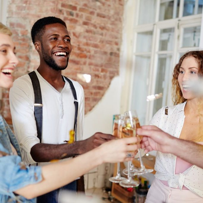 Two young ecstatic couples toasting with champagne while celebrating anniversary of their friendship
